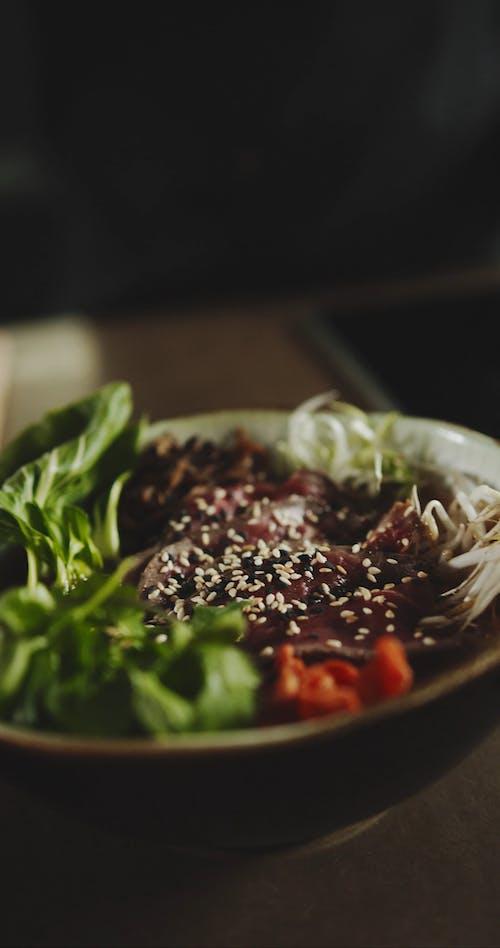 Streuen Sie Von Sesam Auf Eine Rindfleischschale