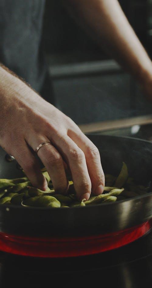 Der Koch, Der Die Sojabohnenschote In Einer Heißen Pfanne Berührt