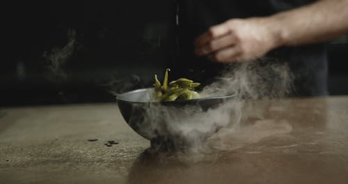 A Chef Sprinkling Salt On An Smoking Bowl Of Edamame