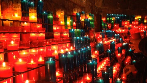 people Lighting Bottled Candles and Placing It On Racks As Prayer Offerings