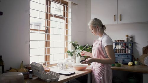 A Woman In The Process Of Baking In A Kitchen