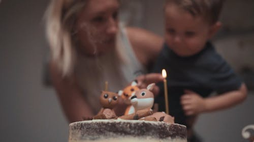 A Mother Helping His Son Blows Off The Candle Flame On His Birthday Cake