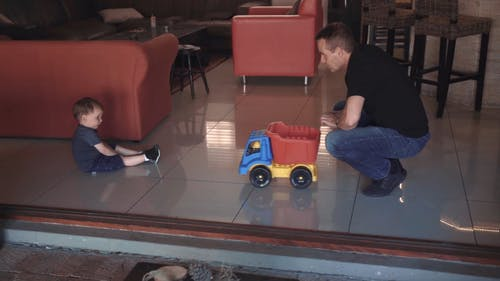 A Father And Son Playing By Pushing Back And Forth A Plastic Toy Truck