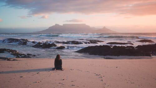 A Woman Seated On The Beach Sand Enjoying The Table Mountain View