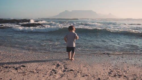 Mutter, Die Ihrem Kind Hilft, Von Einer Stolperursache Durch Die Meereswellen Aufzustehen