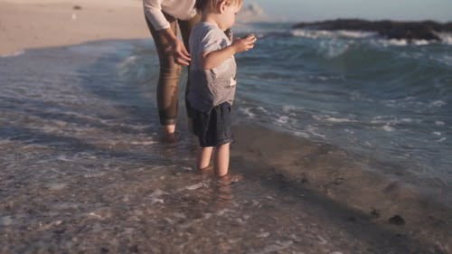 A Mother And Child Standing In The Beach Water Throwing Rocks