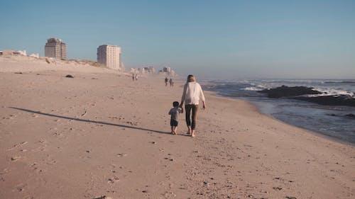 Una Madre E Figlio In Esecuzione Mano Nella Mano Su Una Spiaggia