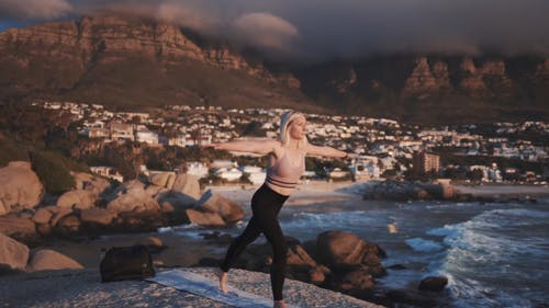 Slow Motion Footage Of A Woman Doing Yoga Outdoors With The View Of A Village By Sea