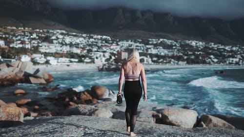 Backside Of A Woman Carrying a Yoga Mat Walking Towards The Rocks On The Seashore