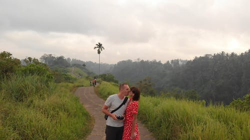 A Couple Sharing A Kiss On A Narrow Road Of The Mountain Top