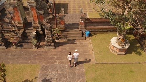 A Couple Walking On The Concrete Facade Leading To The Entrance Of The Temple Grounds