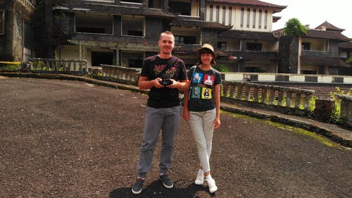 A Couple Standing On The Driveway Of An Abandoned Hotel Building