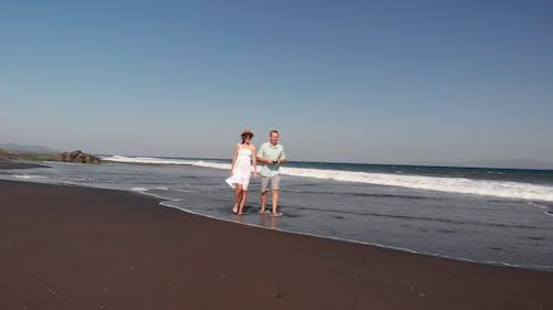 A Couple Walking On Beach Sand Barefoot