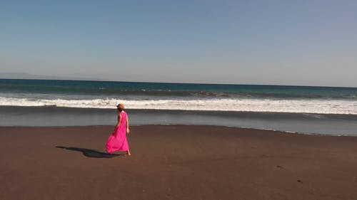 A Barefooted Woman Walking On The Beach Shore