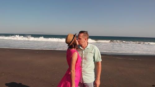 A Couple Sharing A Kiss On The Beach Shore