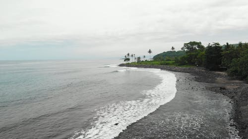 Waves Kissing The Shore Of A Black Sand Beach