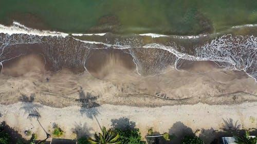 Waves Washing The Shoreline Exposing Black Sand