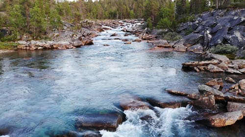 A Rocky River Streaming Down On Rock Formations