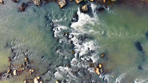 A River Flowing Through Boulders Of Loose Rock