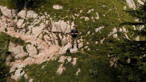 A Man Controlling A Drone Machine Standing On The Mountain Slope