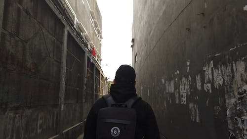 Back View Of A Man Walking In An Alley