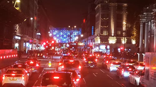 Night Travel On The Busy Street Of London Decorated With Christmas Lights