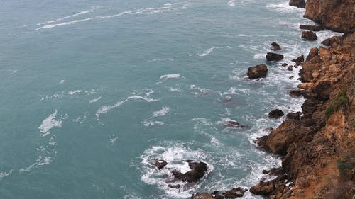 Meereswellen, Die Die Felsen Am Ufer Zusammenstoßen