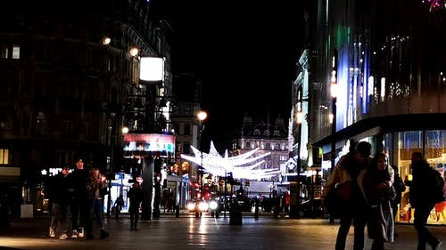 A Busy Street In London At Night During Christmas Season
