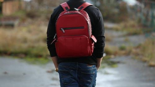 Una Persona Sta Camminando Con Uno Zaino Rosso