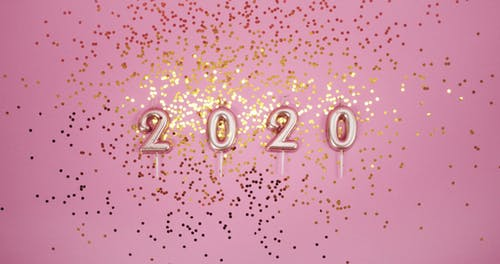 Glitters Of Gold Confetti Over A Pink Surface
