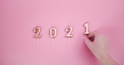 A Person Arranging Number Candles Indicating A Year Date