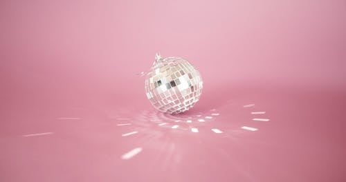 A Small Mirror Ball Bouncing Off Squared Light Reflections In The Pink Surface