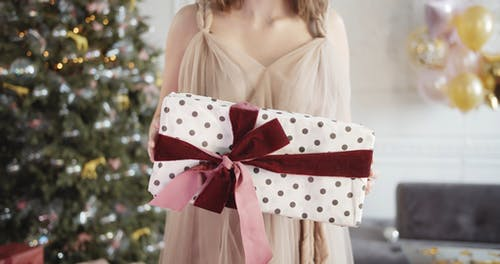 A Woman Holding A Wrapped Christmas Present With Ribbon