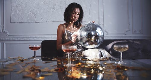 A Woman Rolling A Mirror Ball Producing Dots Of Light Reflection