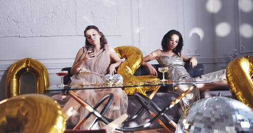 Two Women Seated On A Couch In A party