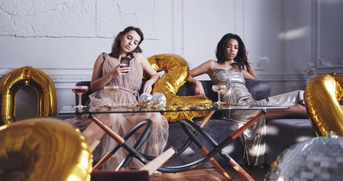 Women Posing For A Photo Shoot On A Couch