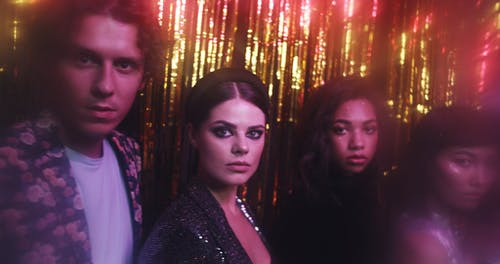 A Group Of People Posing For A Photo Shoot In Front Of The Golden Foil Curtain