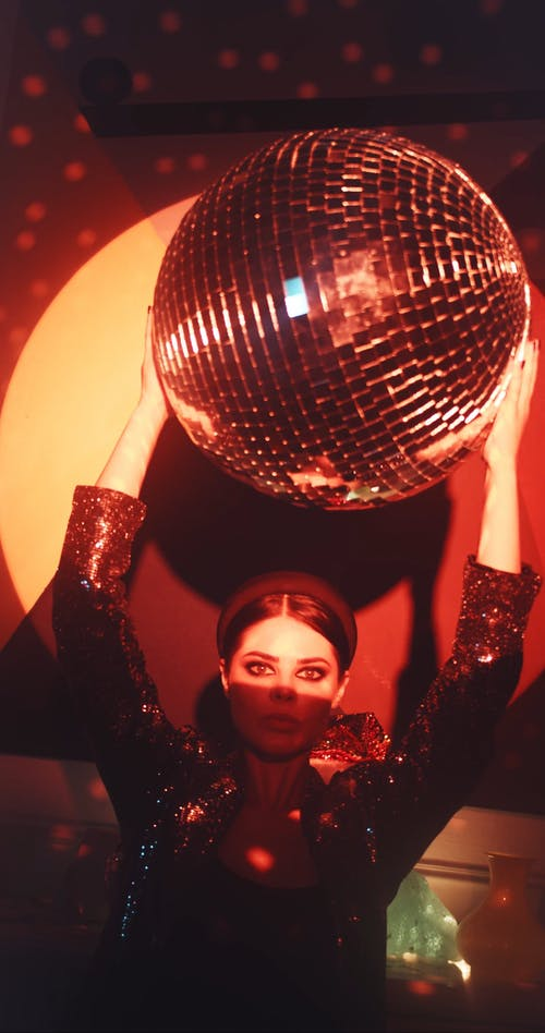 A Woman Holding A Disco Ball Overhead Producing Dots Of Disco Lights
