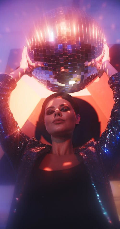 A Woman Holding A Mirror Ball Above Head To Reflect A Spot Light Into Dots Of Small Lights