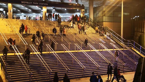 People Going Up And Down The Stairs Leading To The Wembley Park Station