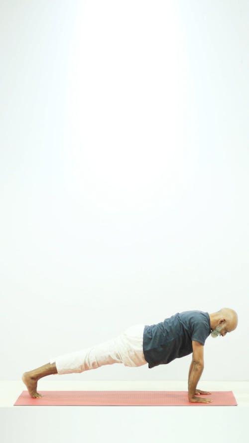 A Man Doing Yoga Exercises On A Floor Mat