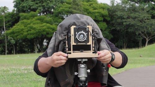 A Person Preparing A Classic Camera Ready For Use