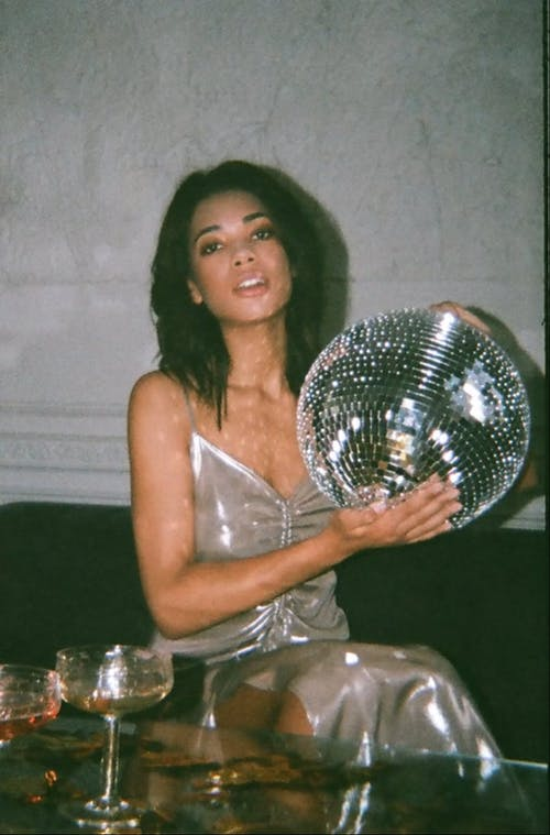Repetitive Footage Of A Woman Holding a Mirror Ball
