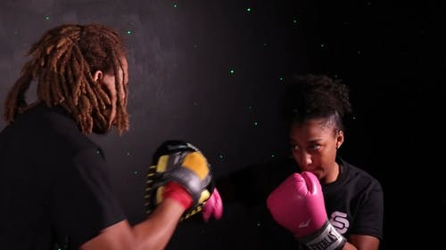A Man Training A Woman In Boxing