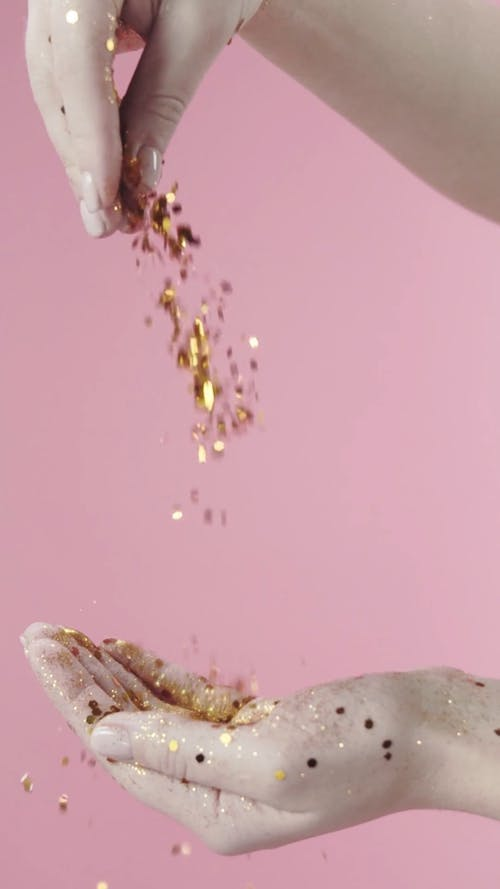 Repetitive Footage Of Sprinkling Gold Glitters On A Hand