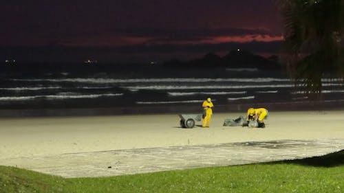 Рабочие очищают пляжный песок от мусора