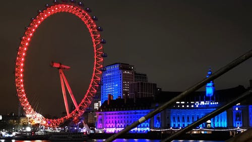 Buildings With Blue Light And Ferris Wheel With Red Light