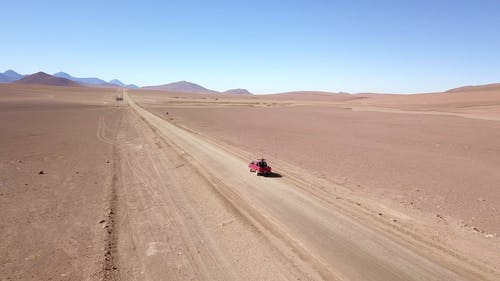 A Vehicle Traveling On A Desert Land