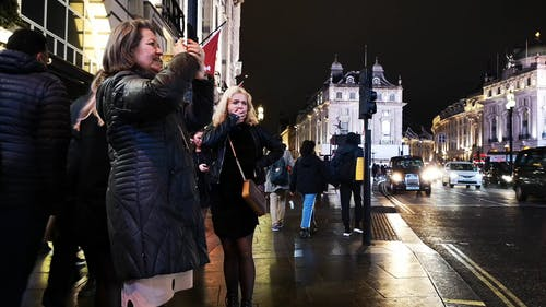 A Woman Recording London Landmarks Using A Cellphone