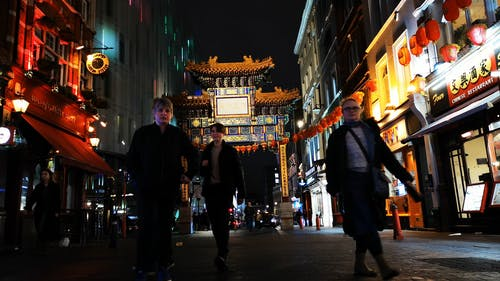 People Passing In And Out Of A China Town Gateway In London